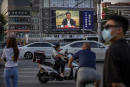 People wearing face masks to protect against the new coronavirus wait to cross an intersection as a large video screen shows Chinese President Xi Jinping speaking in Beijing, Tuesday, June 30, 2020. China approved a contentious national security law that will allow authorities to crack down on subversive and secessionist activity in Hong Kong, a move many see as Beijing's boldest yet to erase the legal firewall between the semi-autonomous territory and the mainland's authoritarian Communist Party system. (AP Photo/Mark Schiefelbein)