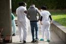 """A patient walks with members of the medical staff in the courtyard of the psychiatric hospital """"EPS de Ville Evrard, Centre psychiatrists du Bois de Bondy"""", on May 7, 2020, in Bondy, during a lockdown aimed at curbing the spread of the COVID-19 pandemic, the novel coronavirus. - The patients of the Centre psychiatrique du Bois de Bondy have been under strict lockdown since the beginning of the COVID-19 outbreak in France mid-March and they haven't received any visits from their relatives since. According to a tribune published by a group French psychiatrists early April 2020, a person affected by a psychiatric disease can suffer 1.5 or 2 times more often, compared to the rest of the population, from associated conditions, such as cardiovascular disorders, diabetes or hypertension, and are therefore more vulnerable to Covid-19. (Photo by Loic VENANCE / AFP)"""