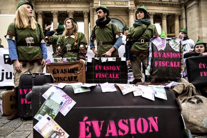 Des militants d'Emmaüs manifestent contre l'évasion fiscale devant l'Assemblée nationale, à Paris, le 10 décembre2018.