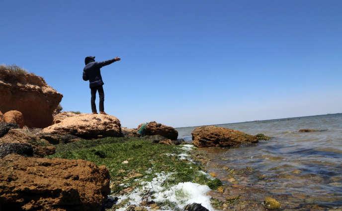 Un homme pointe l'horizon sur une île desKerkennah, en Tunisie, en juin 2018. L'archipel est un haut lieu de départ de migrants vers l'Italie.