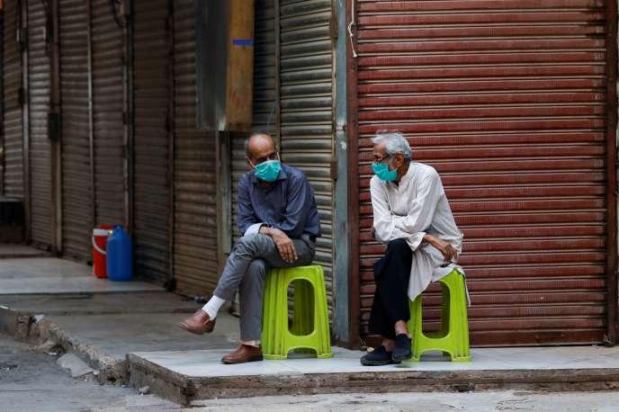 Des commerçants, portant des masques de protection, devant leurs boutiques fermées, à Karachi, au Pakistan, le 1er juillet. Les autorités ont réimposé des mesures de confinement dans certaines zones du pays afin d'endiguer la propagation du coronavirus SARS-CoV-2.