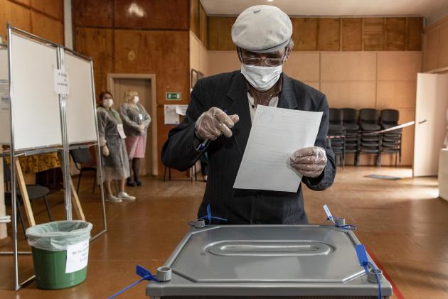 Un homme vote àVisim, un village de l'Oural, le 1er juillet.Pour éviter une trop forte affluence dans les bureaux de vote, le scrutin s'est déroulé sur une semaine et les électeurs devaient se munir d'un masque et de gants.