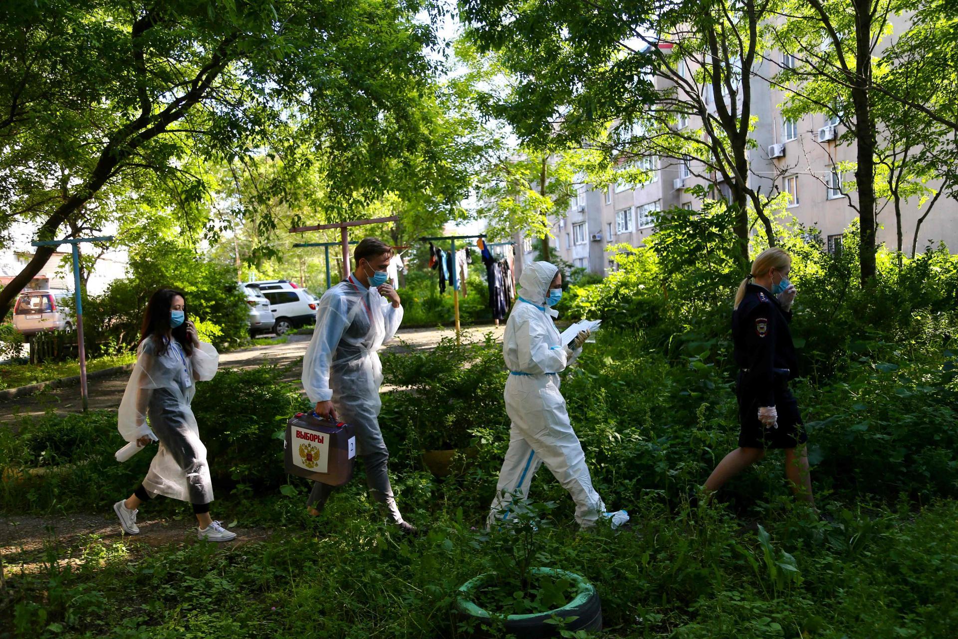 Des membres d'une commission électorale se déplacent chez des particuliers avec un bureau de vote mobile, àVladivostok, le 1er juillet.