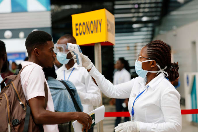 Un agent de santé vérifie la température d'un voyageur à l'aéroport international de Kotoka, à Accra, au Ghana, le 30 janvier 2020.