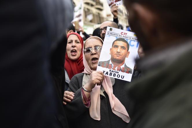 Une Algérienne brandit un portrait de Karim Tabbou lors d'une manifestation antigouvernementale à Alger, le 24janvier 2020.