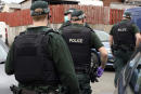 In this photo issued Thursday July 2, 2020, by the Police Service of Northern Ireland (PSNI) showing police during a raid in Operation Venetic, an investigation on Encrochat, a military-grade encrypted communication system used by organised criminals trading in drugs and guns. Police have released information saying that officers in the UK had arrested 307 suspects, recovered 106 Encrochat devices and seized many millions in bank notes. (PSNI via AP)
