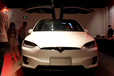 People wearing face masks following the coronavirus disease (COVID-19) outbreak check a Tesla Model X sport utility vehicle at a new Tesla showroom in Shanghai, China May 8, 2020. Picture taken May 8, 2020. REUTERS/Yilei Sun - RC2TMG9E4AZZ