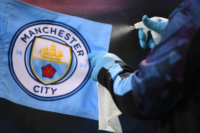 Un membre du personnel désinfecte le drapeau de corner, alors que le jeu reprend à huis clos lors du match Manchester City-Liverpool, à l'Etihad Stadium, à Manchester, le 2 juillet 2020.