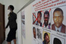 A red cross is seen drawn on the face of Augustin Bizimana (R), one of the most-wanted fugitives from the 1994 Rwandan genocide, next to the red-crossed face of Felicien Kabuga (L), who was arrested last week in Paris, on a wanted poster at the Genocide Fugitive Tracking Unit office in Kigali, Rwanda, on May 22, 2020. - On May 22, 2020, the United Nations (UN) tribunal said it had at an unknown date come into possession of human remains from a grave site in Pointe Noire in the Republic of the Congo. Extensive analysts showed that Bizimana had died in 2000 after all. The news dashed the hopes of victims for justice, just days after the arrest of Felicien Kabuga, one of the last fugitives from the genocide, who had been on the run for three decades. (Photo by Simon Wohlfahrt / AFP)