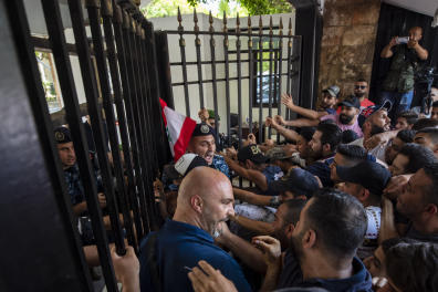Anti-government protesters try to enter the main gate of the Lebanese interior ministry as they shout slogans against minister Mohammed Fahmi during a protest, in Beirut, Lebanon, Friday, July 3, 2020. (AP Photo/Hassan Ammar)