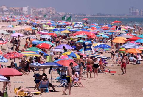 TOPSHOT - People enjoy a day at the Nord Beach in Gandia, near Valencia on July 1, 2020. The European Union reopened its borders to visitors from 15 countries but excluded the United States, where coronavirus deaths are spiking once again, six months after the first cluster was reported in China. / AFP / JOSE JORDAN