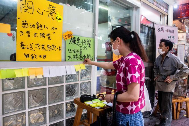 Une femme colle une note blanche sur le«mur de Lennon» devant un restaurant prodémocratie à Hongkong, le 3 juillet 2020, en réponse à la loi sur la sécurité nationale.