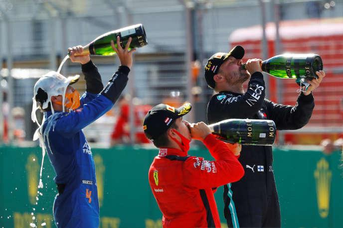 Valtteri Bottas (Mercedes), en noir, Lando Norris (McLaren), en bleu, et Charles Leclerc (Ferrari), en rouge, célèbrent leur podium au Grand Prix d'Autriche de Formule 1, le 5 juillet.