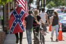 A man wears a Confederate flag while walking with others, Friday, July 3, 2020, in Marion, Va. (Andre Teague/Bristol Herald Courier via AP)