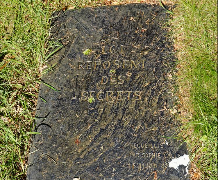 Dans une édition précédente de « Lieux mouvants», Sophie Calle a recueilli, auprès des habitants du pays, des secrets, lourds ou plus légers, qui ont ensuite été enterrés sous cette dalle de schiste dans l'enclos de Burthulet. L'œuvre est la propriété du fonds régional d'art contemporain.