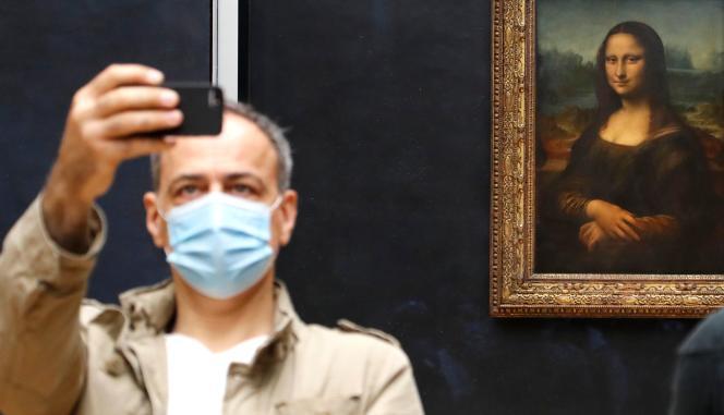 Un visiteur lundi 6 juillet 2020 devant le portrait de Mona Lisa, le célèbre tableau de Léonard de Vinci.