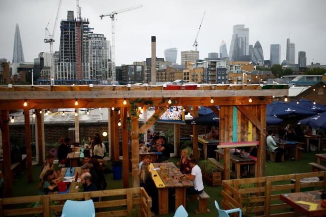 Des clients installés à la terrasse d'un bar le jour du déconfinement, à Londres, le 4 juillet.