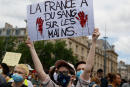 A protester holds a sign reading 'France has blood on its hands' during a rally as part of the 'Black Lives Matter' worldwide protests against racism and police brutality, on Place de la Republique in Paris on June 13, 2020. - A wave of global protests in the wake of US George Floyd's fatal arrest magnified attention on the 2016 death in French police custody of Adama Traore, a 24-year-old black man, and renewed controversy over claims of racism and brutality within the force. (Photo by Thomas SAMSON / AFP)