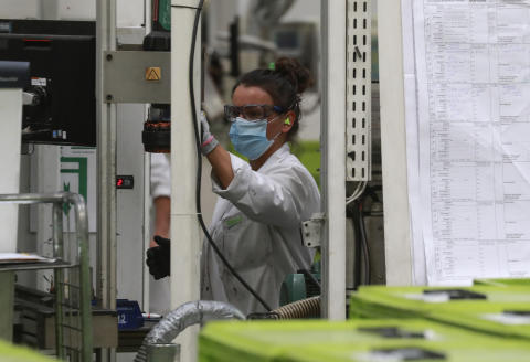 An employee works at a factory of manufacturer Valeo in Etaples, near Le Touquet, northern France on May 26, 2020 during a visti of French President as part of the launch of a plan to rescue the French car industry. (Photo by Ludovic MARIN / POOL / AFP)