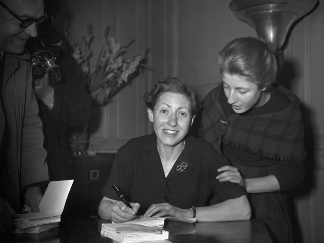 L'écrivaine Béatrix Beck, avec sa fille (à droite), dédicace des exemplaires de « Léon Morin, prêtre», à Paris à la fin de 1952, peu après avoir reçu le prix Goncourt.