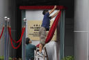 Workers take off a curtain after attend an opening ceremony for China's new Office for Safeguarding National Security in Hong Kong, Wednesday, July 8, 2020. China's new national security office in Hong Kong got off to an early start on Wednesday with an official opening amidst heavy police presence. (AP Photo/Kin Cheung)