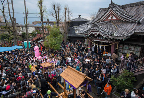 KAWASAKI, JAPAN - APRIL 06: A general view as people pose for photos in front of a large pink phallic-shaped 'Mikoshi' at the Wakamiya Hachimangu shrine during Kanamara Matsuri (Festival of the Steel Phallus) on April 6, 2014 in Kawasaki, Japan. The Kanamara Festival is held annually on the first Sunday of April. The penis is the central theme of the festival, focused at the local penis-venerating shrine which was once frequented by prostitutes who came to pray for business prosperity and protection against sexually transmitted diseases. Today the festival has become a popular tourist attraction and is used to raise money for HIV awareness and research. (Photo by Chris McGrath/Getty Images)