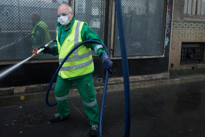 Nettoyage des trottoirs par un agent de propreté de la ville de Paris, le 29 avril.