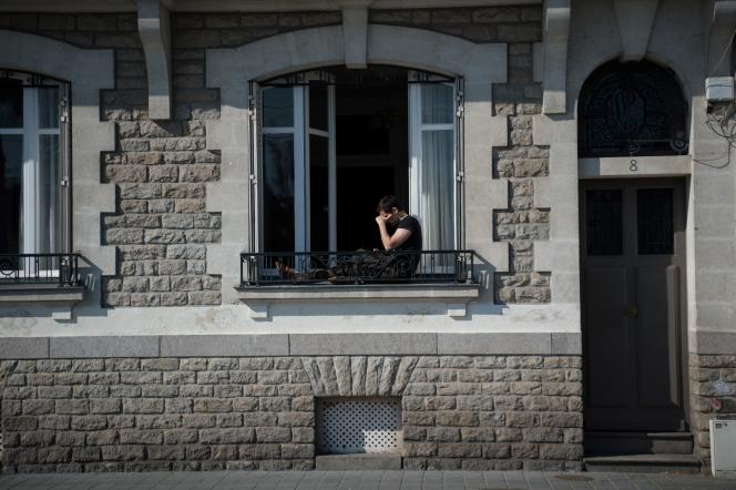 Un homme prend l'air depuis le bord de sa fenêtre, pendant le confinement, à Nantes, le 26 mars.