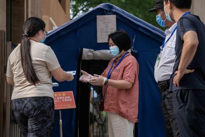 Contrôle d'identité à l'entrée d'une école, à Pékin, le 8 juillet, deuxième jour des épreuves du Gaokao, l'équivalent du baccalauréat.