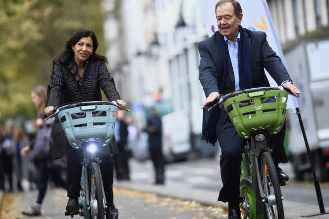 Anne Hidalgo et Patrick Ollier sur les nouveaux vélos Vélib'Métropole, près du bassin de La Villette à Paris, en octobre 2017.