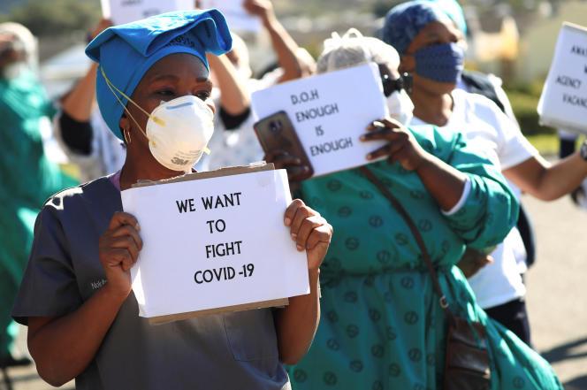 Des agents de santé brandissent des pancartes pour protester contre le manque d'équipement de protection individuelle face au Covid-19, au Cap, le 19 juin 2020.