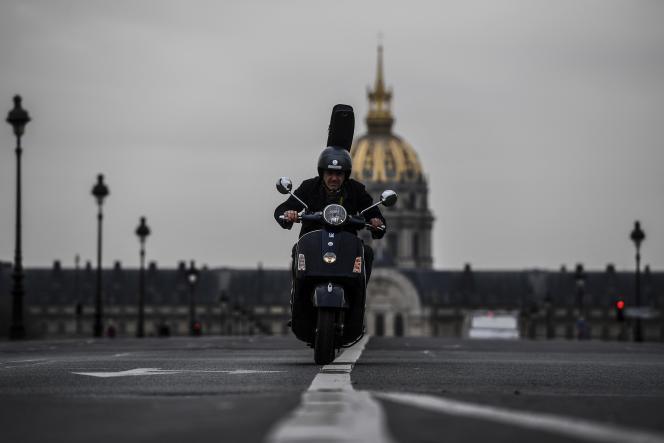Un homme roule en scooter devant les Invalides, le 17 mars.