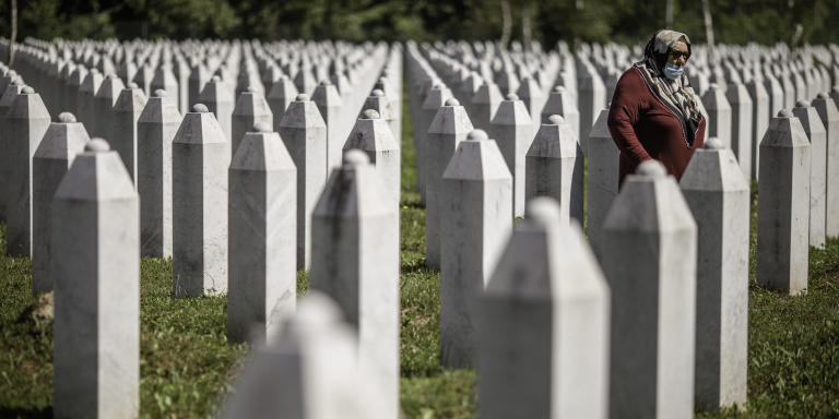 A Bosnian Muslim woman walks between graves of victims of Srebrenica genocide, at the cemetery in Potocari, near Srebrenica July 9, 2020. Photo Damir Sagolj for Le Monde