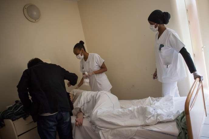 Un psychiatre et des membres du personnel soignant vérifient la température d'un patient qui s'est remis du COVID-19 à l'hôpital psychiatrique de Bondy (Seine-Saint-Denis), le 7 mai.