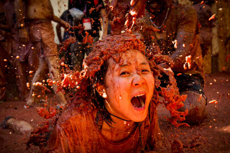 A reveller covered in tomato pulp participates in the annual