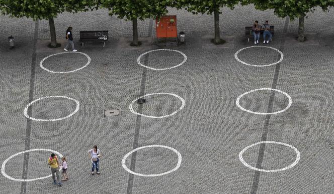 Des cercles sur un trottoir de la vieille ville de Düsseldorf rappellent à la population les mesures de distanciation physique prises pour endiguer l'épidémie de Covid-19 en Allemagne, mardi 14 juillet 2020.