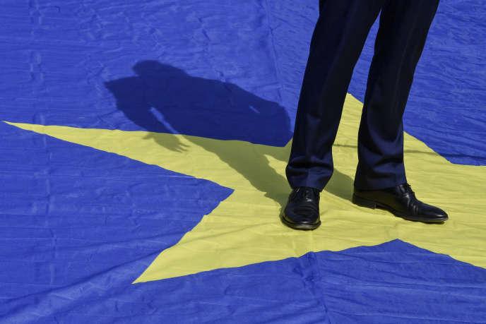 Le commissaire européen à la justice, Didier Reynders, est debout sur le drapeau européen, à Bruxelles le 9 mai 2020.
