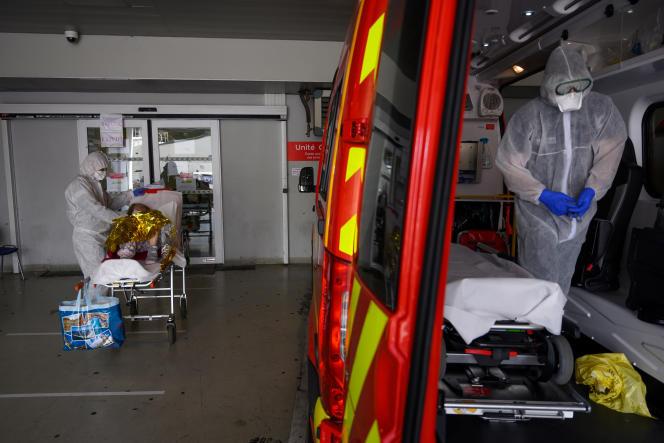 Un pompier conduit aux urgences une femme de 84 ans ayant des symptômes du Covid-19, à l'hôpital de la Timone, à Marseille (Bouches-du-Rhône), le 15 avril.