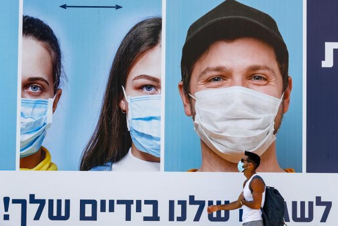 Un homme masqué passe devant un panneau d'affichage montrant d'autres visages masqués et des mesures de distance sociale adéquates, à Tel-Aviv, le 17juillet 2020.