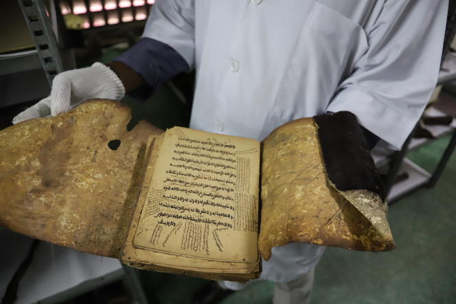 Francis Tagro Gnoleba et Antonio Gnako, conservateurs du Musée des civilisations d'Abidjan, prennent soin des 15 210 pièces des collections: ici, un coran ancien.