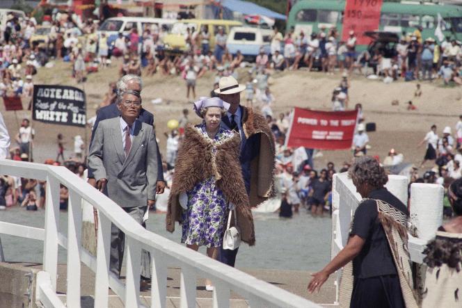 La reine d'Angleterre, ElizabethII, et le duc d'Edinbourg arrivent à Waitangi, le 6février 1990, pour fêter l'anniversaire des 150 ans du traité de Waitangi. Derrière eux, des Maoris manifestent.