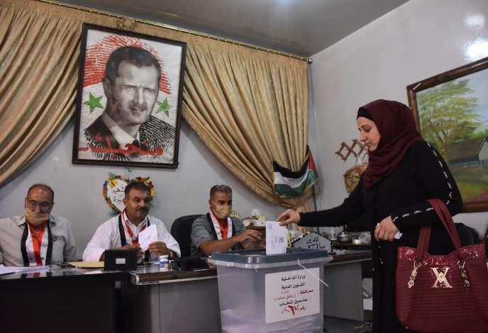 Dans un bureau de vote près d'Alep en Syrie, dimanche 19 juillet. Le portrait du président, Bachar al-Assad, est suspendu au-dessus des assesseurs.