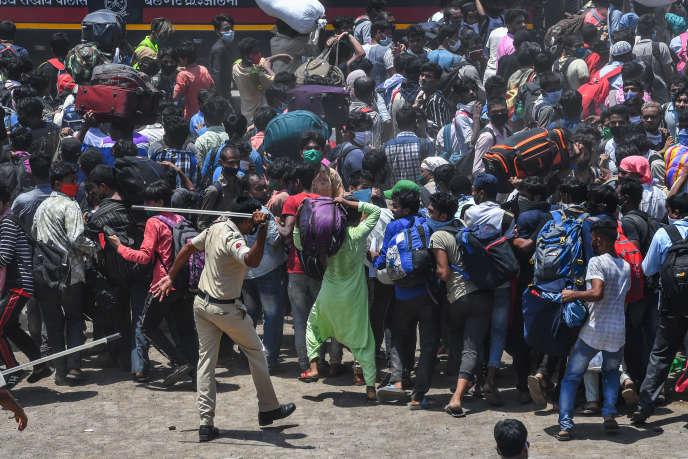 Un policier use de son baton pour disperser des migrants ne disposant pas de billet pour monter dans le train les ramenant chez eux, dans une gare de Bombay, le 19 mai 2020.