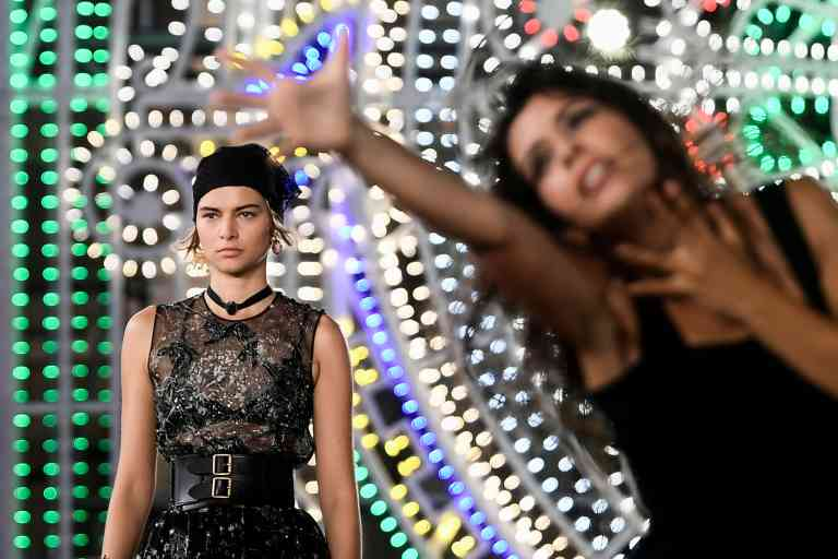 A model presents a creation for Dior during the 2021 Dior Croisiere (Cruise) fashion show on July 22, 2020 in Lecce, southern Italy as a dancer performs next to her. / AFP / Filippo MONTEFORTE