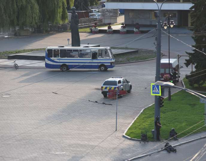 Des forces de police entourent le bus dans lequel la prise d'otages s'est déroulée, mardi 21juillet à Loutsk, dans l'ouest de l'Ukraine.