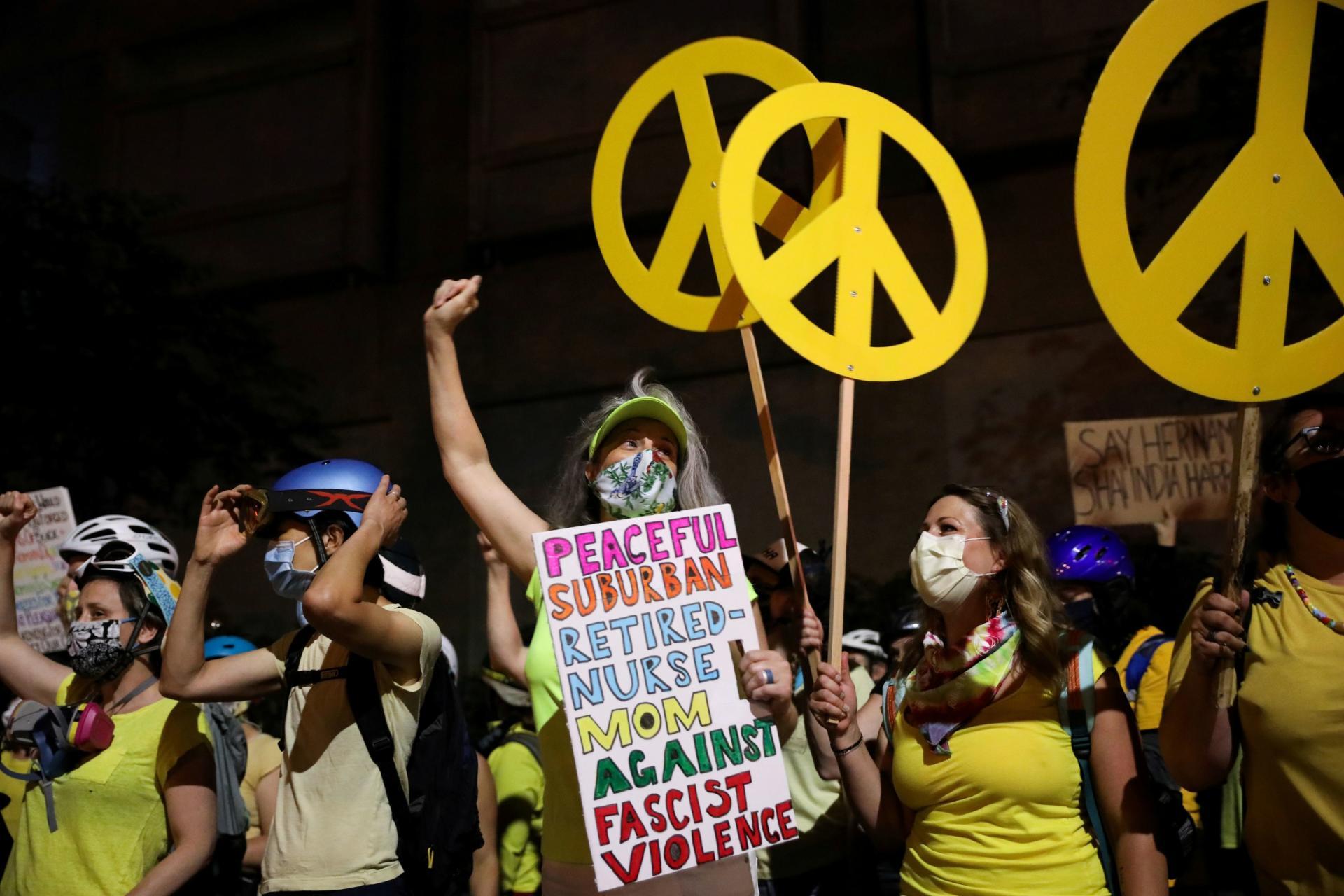 Des mères de famille brandissent des symboles «peace and love» pour manifester leur colère contre les violences policières, à Portland, le 21juillet.