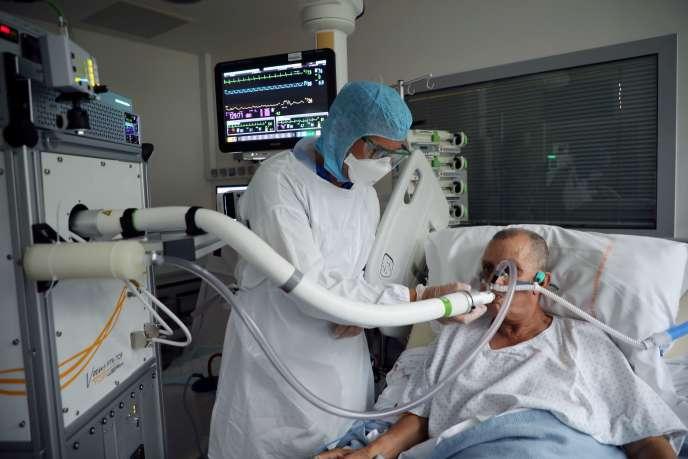 Christian George, directeur adjoint de l'Institut de recherches sur la catalyse et l'environnement de Lyon (Ircelyon), aide un patient atteint du Covid-19 à utiliser un appareil d'analyse de l'air expiré, le 22 juillet 2020.