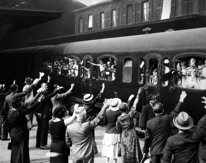 Des enfants,avant de partir en vacances, saluent leurs parents dans une gare parisienne, dans les années 1930.