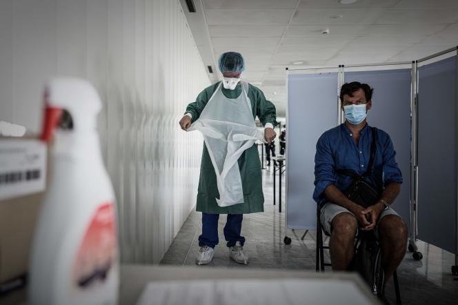 Le personnel médical se prépare à prélever un échantillon dans une cabine de dépistage gratuite de Covid-19 installée dans le hall d'arrivée de l'aéroport international de Bordeaux-Mérignac, le 23 juillet 2020.
