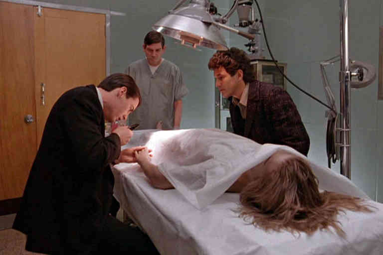 Watched by Canadian actor Michael Ontkean (as Sheriff Harry S. Truman) (right), American actor Kyle MacLachlan (as Special Agent Dale Cooper) examines the hand of German-born American actress Sheryl Lee (as the deceased Laura Palmer) in a scene from the pilot episode of the television series 'Twin Peaks,' originally broadcast on April 8, 1990. An unidentified actor as a morgue attendant (known as 'Jim') stands at the end of the gurney. (Photo by CBS Photo Archive/Getty Images)
